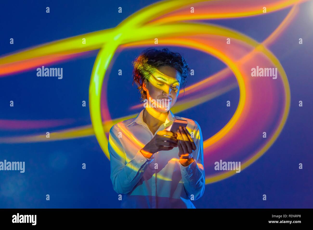 Woman using smart phone with projection - Stock Image