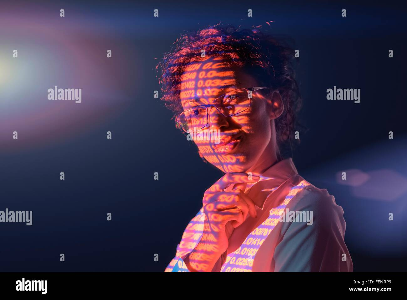 Businesswoman in thought with projected financial numbers on dark background - Stock Image