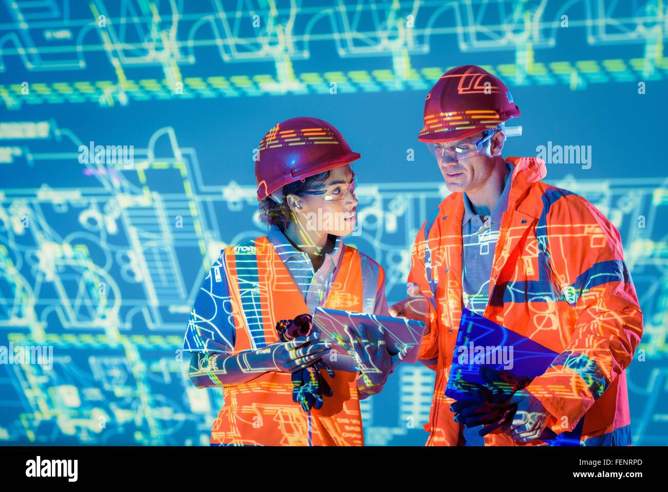 Engineers with digital tablet and projected plans - Stock Image