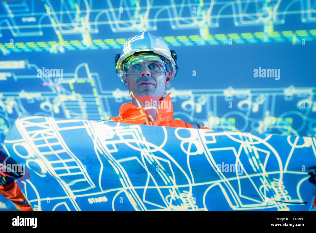 Engineer with blueprint and projected plans - Stock Image