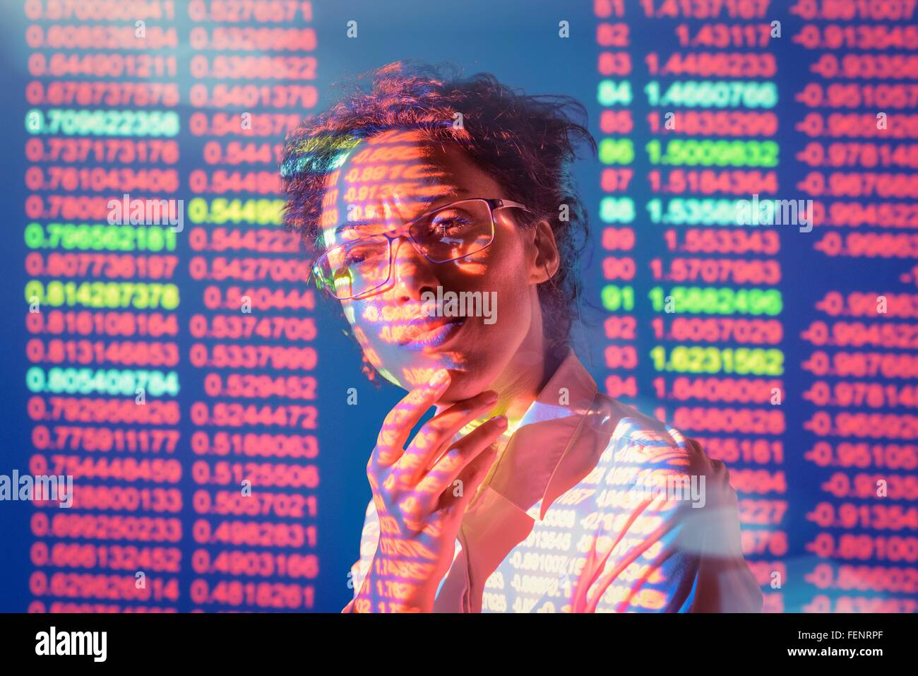 Businesswoman in thought with projected financial numbers - Stock Image