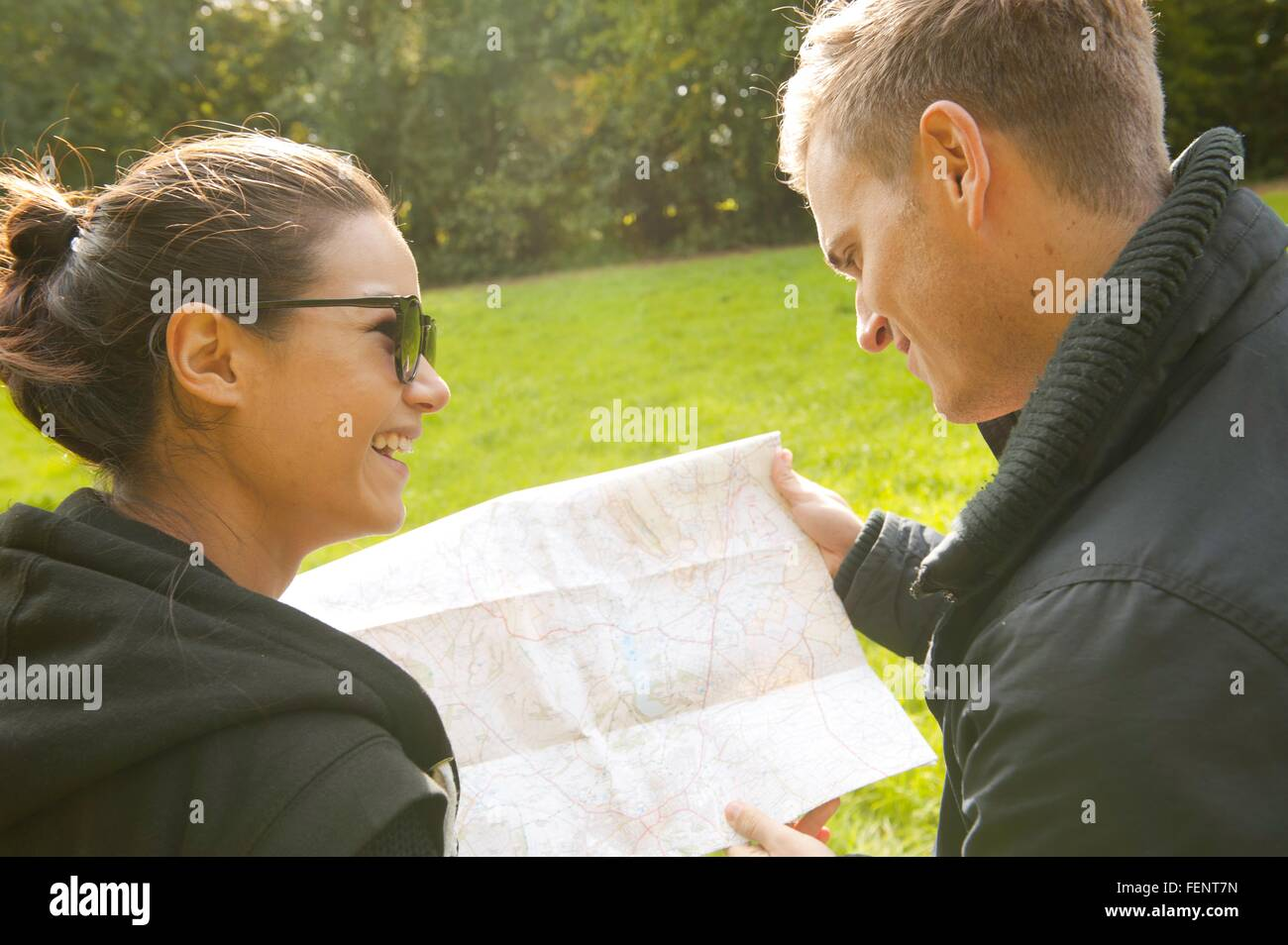 Over the shoulder view of young couple reading map in field - Stock Image
