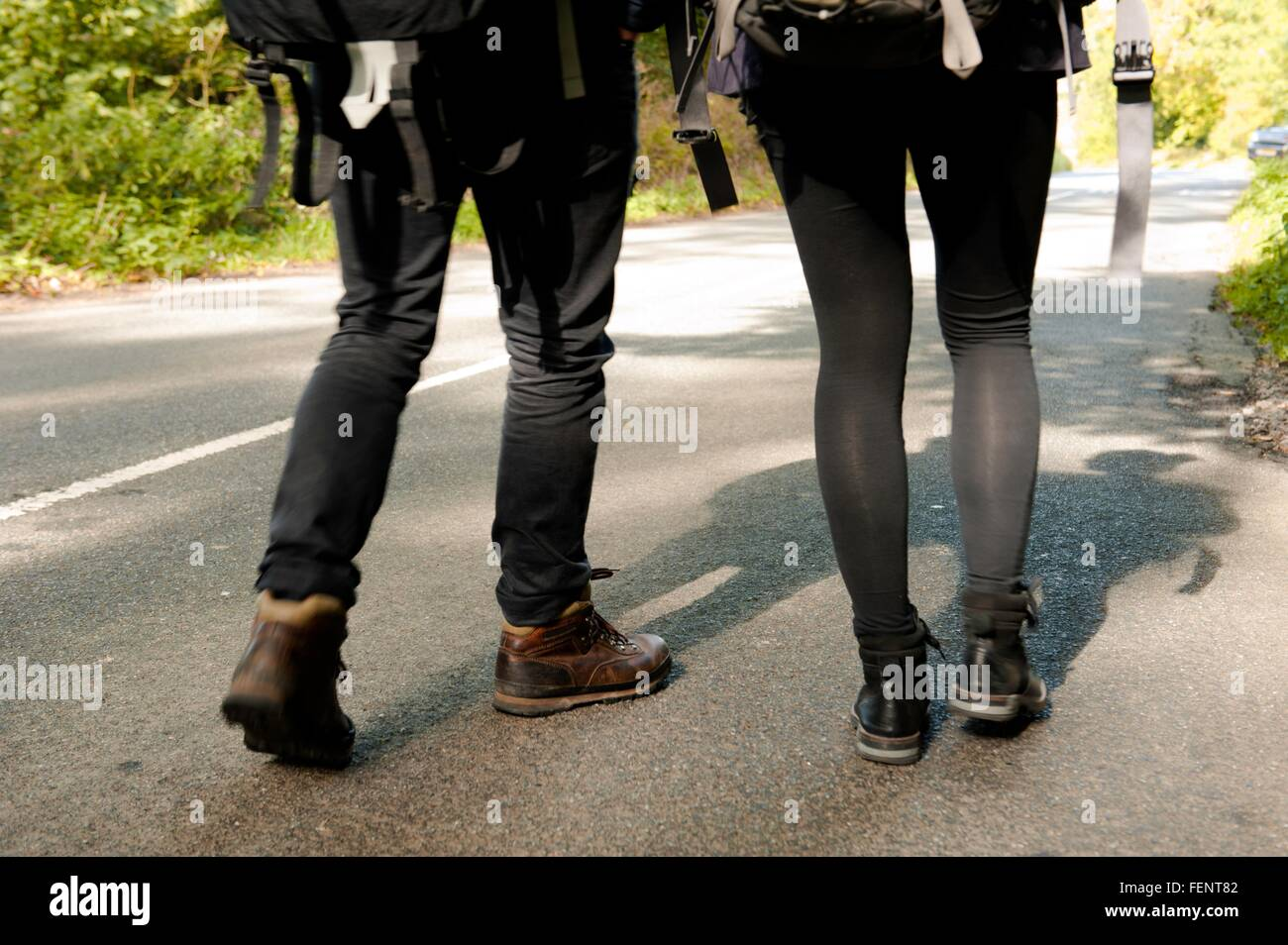 Waist down rear view of young hiking couple on rural road - Stock Image