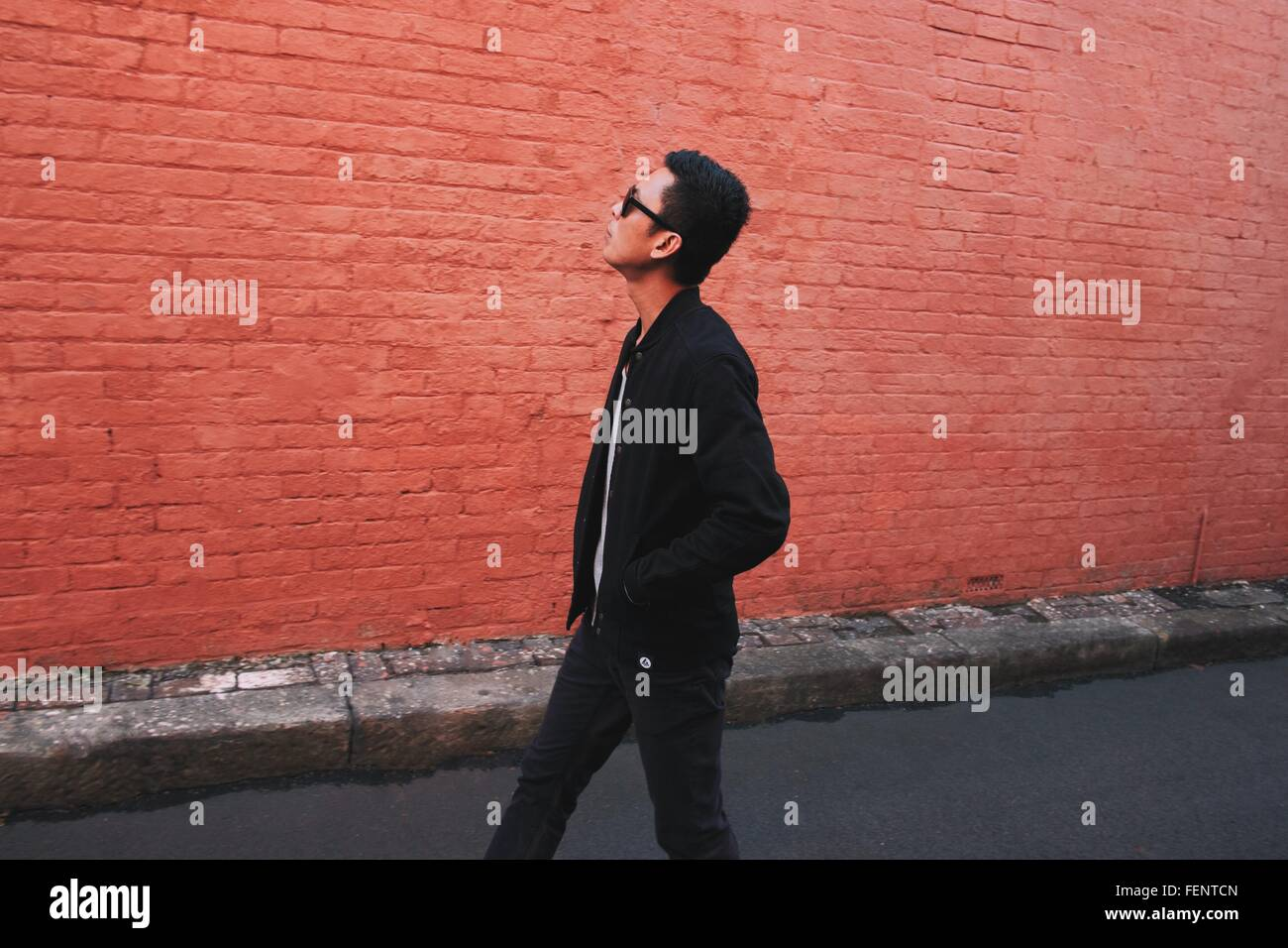 Side View Of Fashionable Young Man Walking On Street Against Red Brick Wall - Stock Image