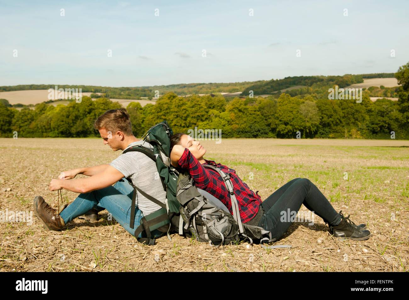 Young hiking couple sitting back to back in field, Great Missenden, Buckinghamshire, U.K - Stock Image