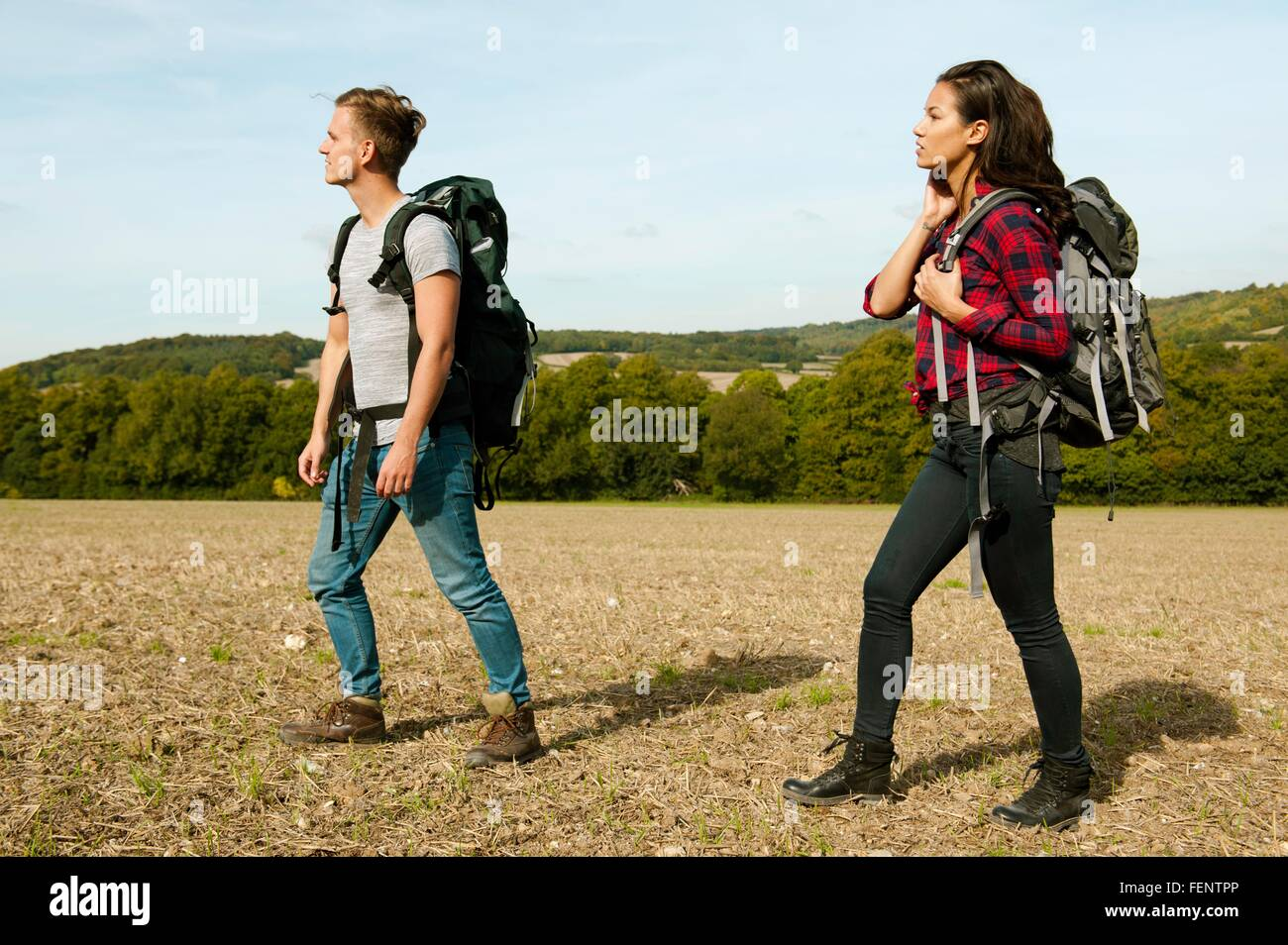 Young couple hiking across in field, Great Missenden, Buckinghamshire, U.K - Stock Image