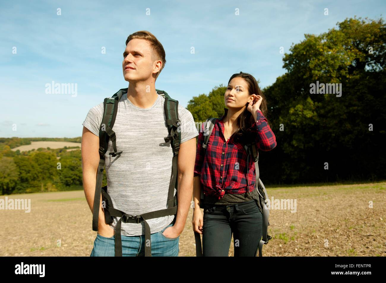 Young couple hiking in field, Great Missenden, Buckinghamshire, U.K - Stock Image