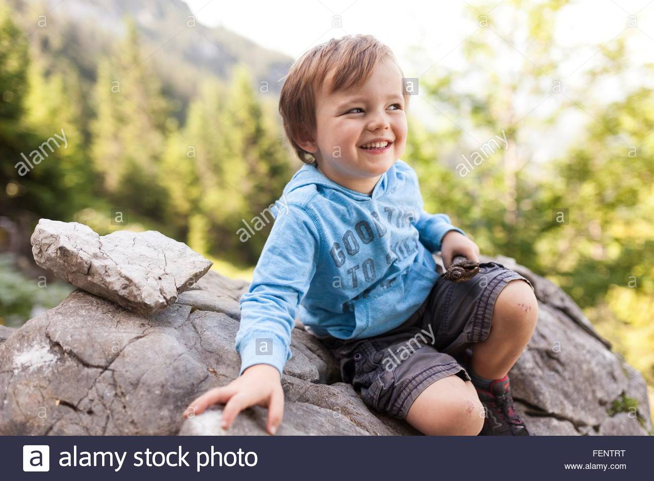 Portrait of young boy sitting on rock - Stock Image