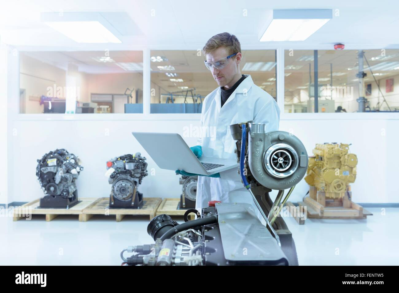 Scientist using laptop in turbo charger automotive research laboratory - Stock Image