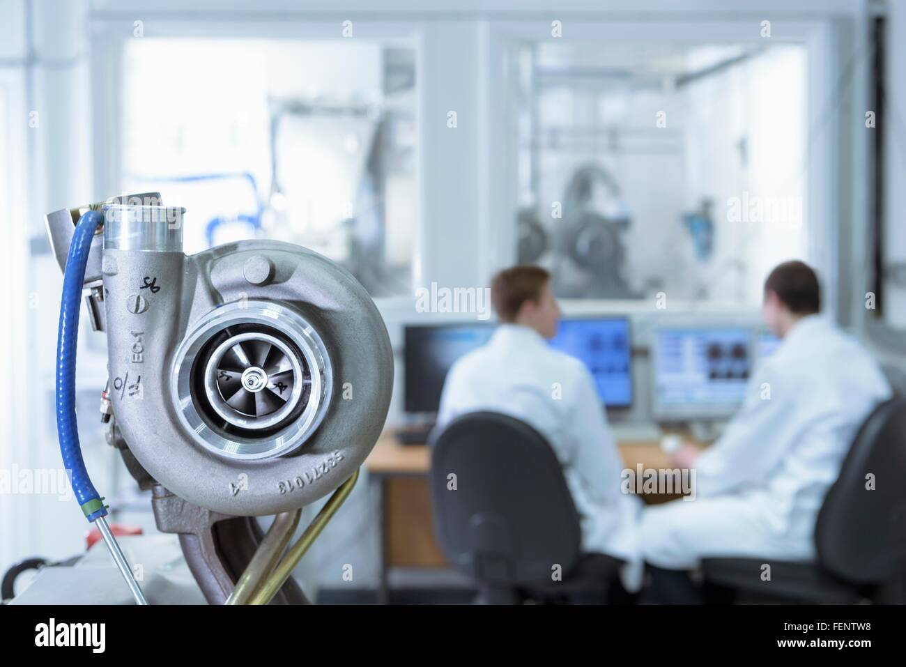 Scientists working at computers in turbo charger automotive research laboratory - Stock Image