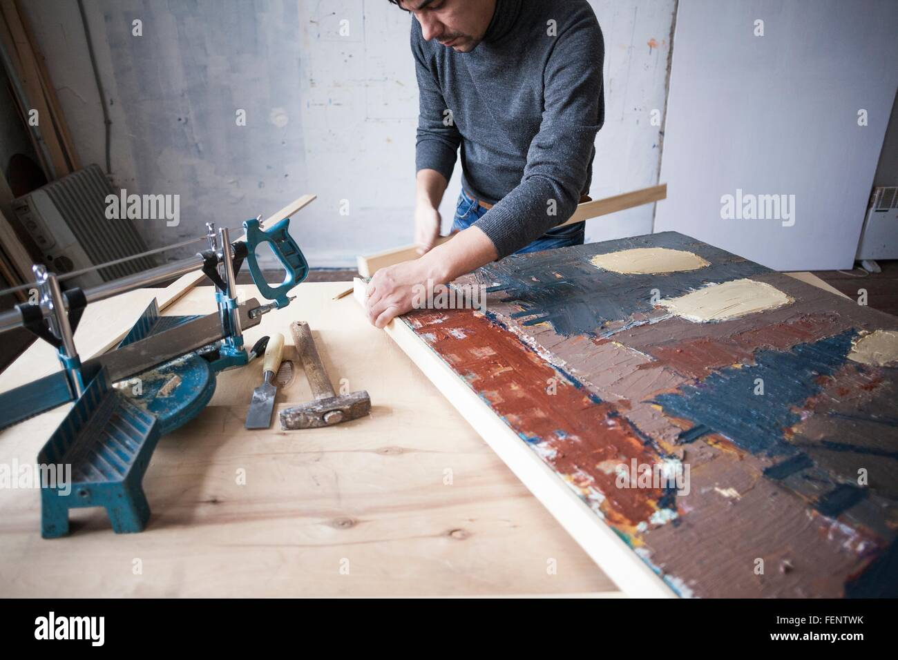 Male artist, framing artwork - Stock Image