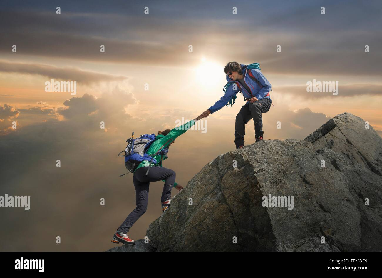 Climber helping partner reach mountain top, Mont Blanc, France - Stock Image
