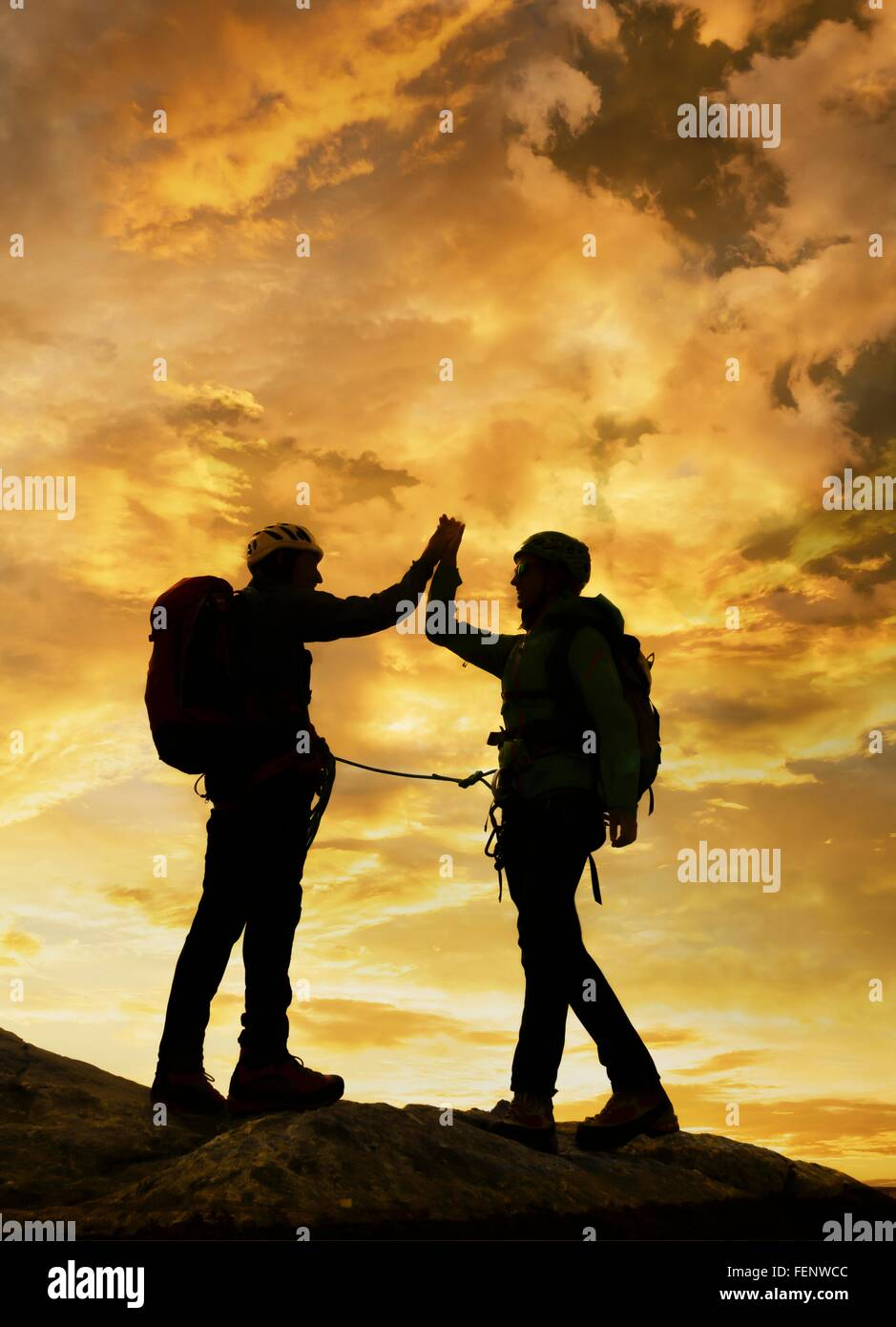 Climbers exulting on mountain top at sunset, Mont Blanc, France - Stock Image