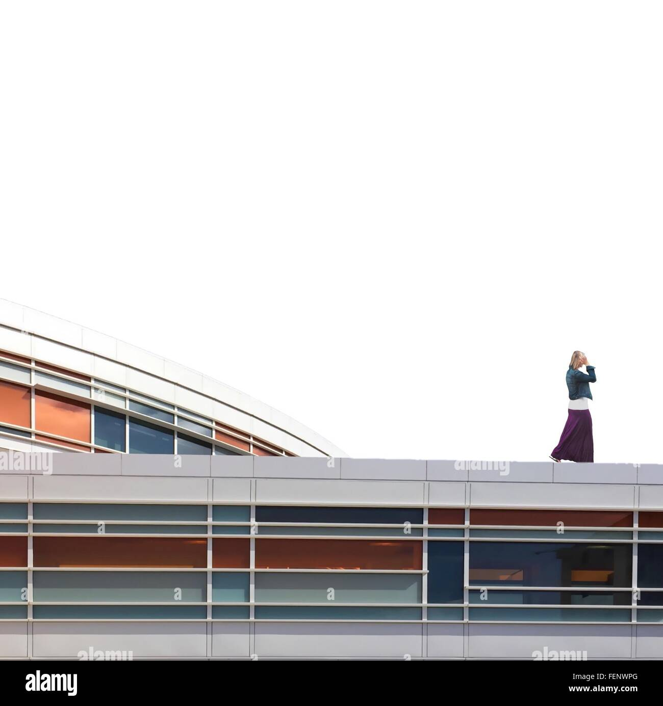 Side View Of Woman Walking On Top Of Building - Stock Image