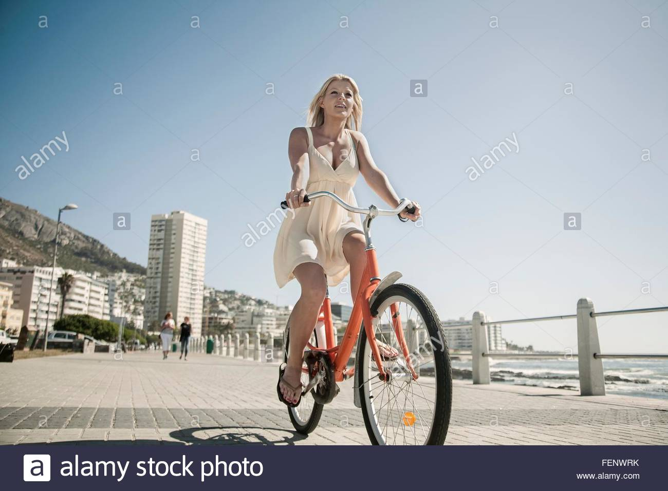 Young woman cycling on seafront, Cape Town, South Africa - Stock Image