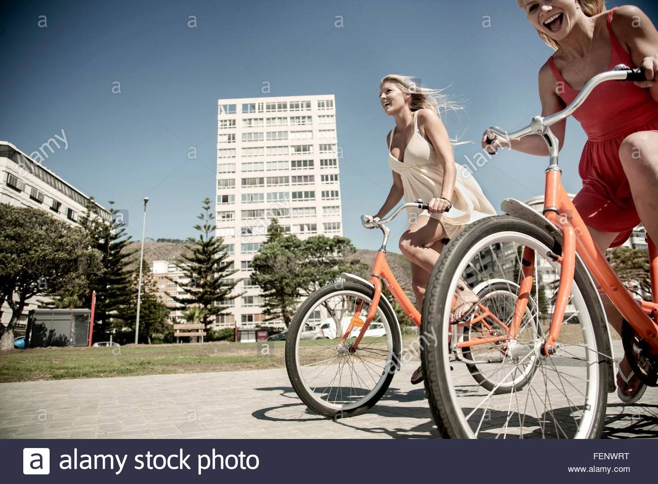 Young women cycling past buildings, Cape Town, South Africa - Stock Image