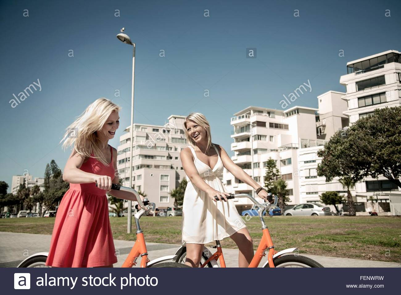 Young women walking with bicycle past buildings, Cape Town, South Africa - Stock Image