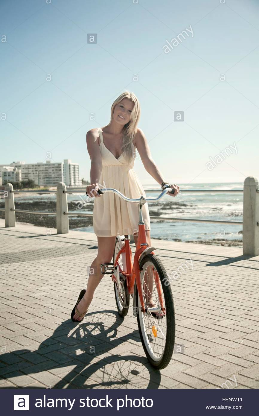 Young woman with bicycle on seafront, Cape Town, South Africa - Stock Image