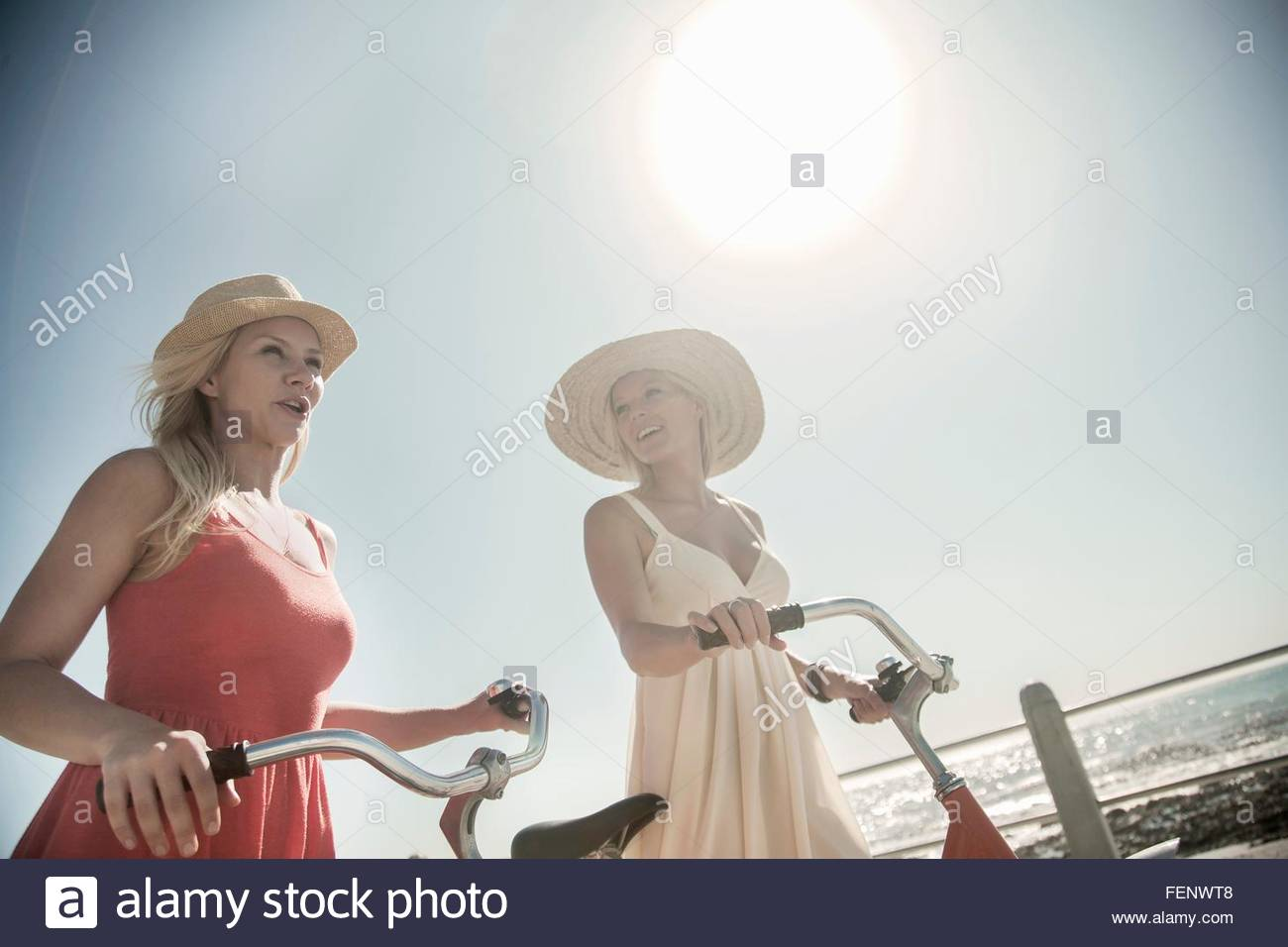 Young women walking with bicycle on seafront - Stock Image