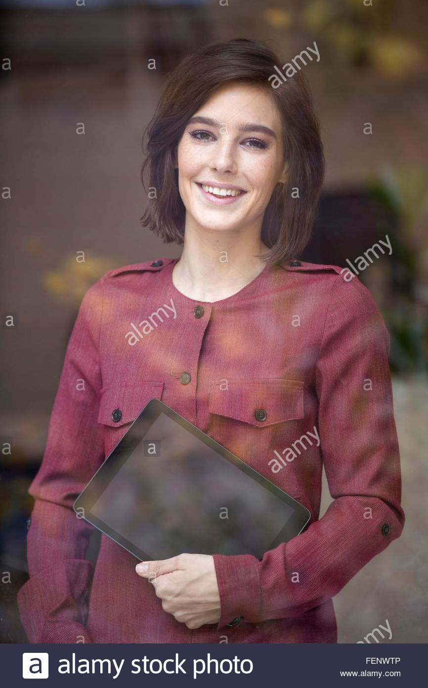Portrait of businesswoman carrying digital tablet looking through window - Stock Image