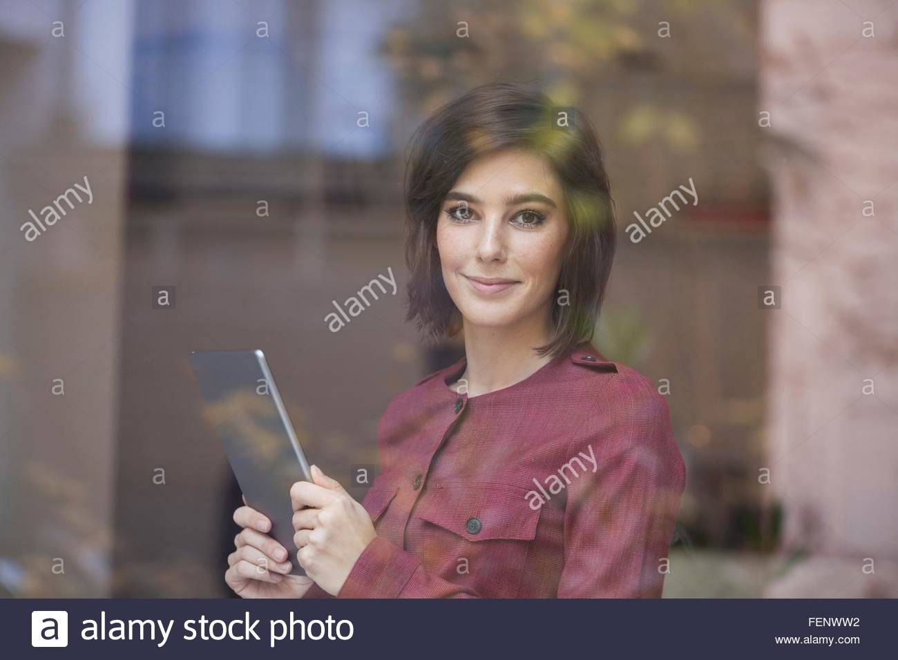 Portrait of businesswoman holding digital tablet looking through window - Stock Image