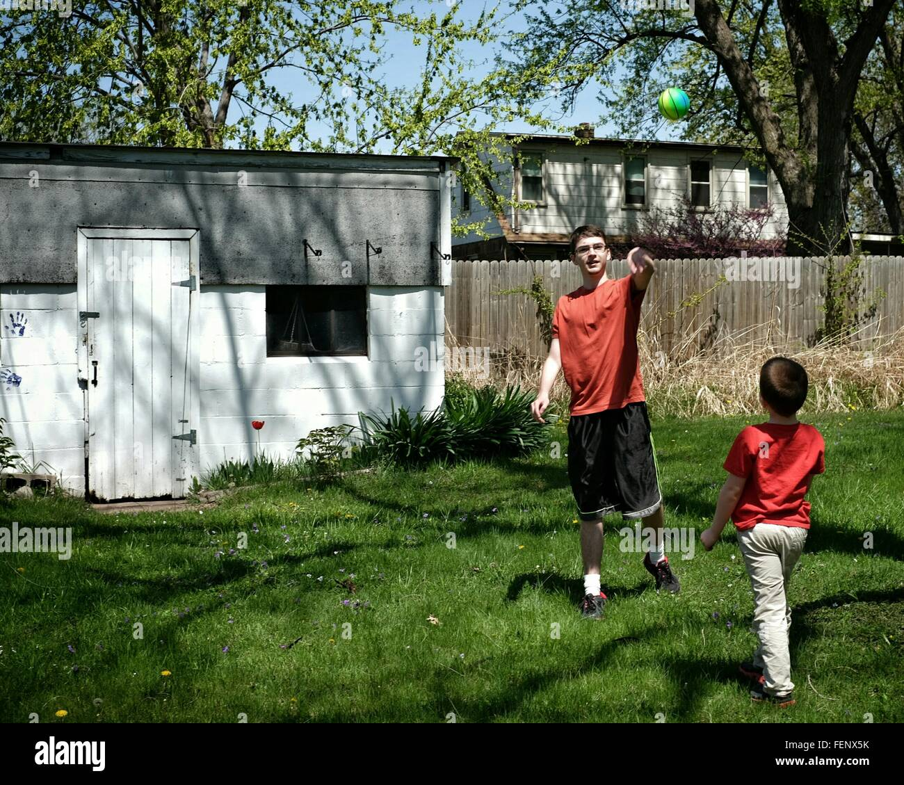Boy Pointing Ball While Playing With Brother In Yard - Stock Image