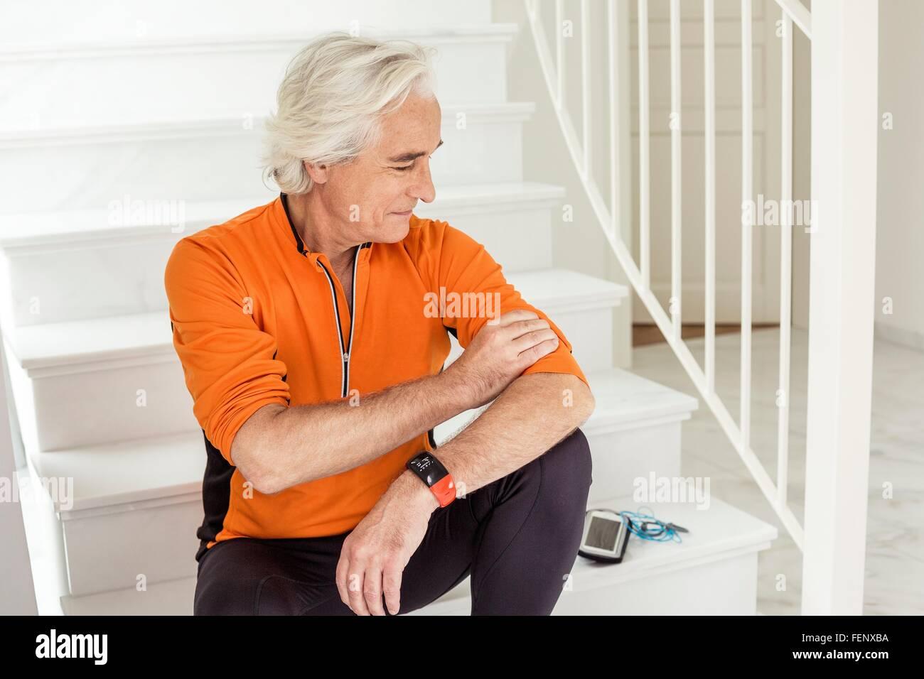 Senior man sitting on staircase preparing for run - Stock Image