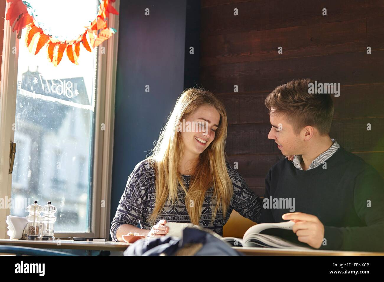 Young couple on date in cafe reading magazine Stock Photo