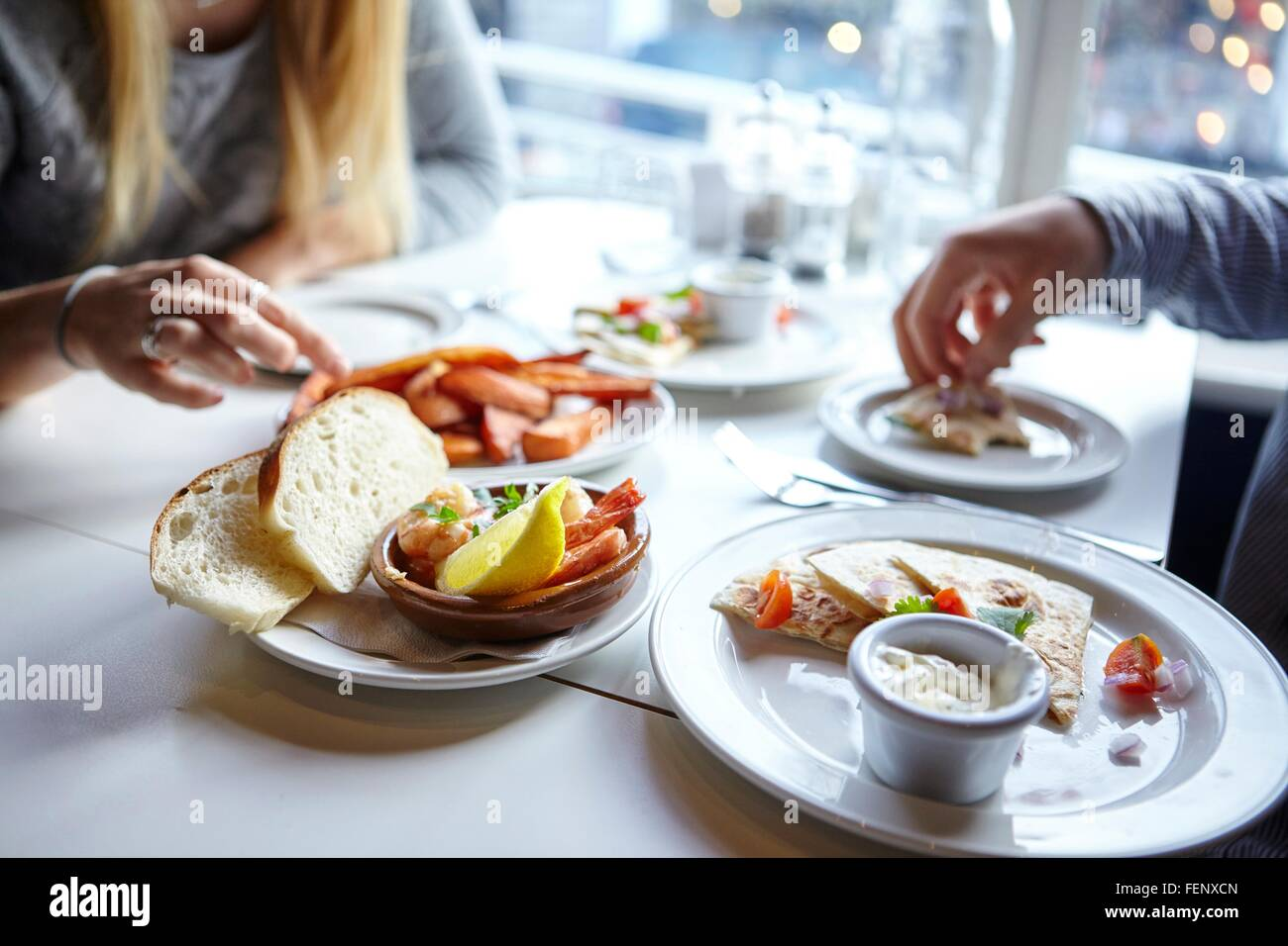Cropped shot of young couples hands eating finger food in cafe - Stock Image
