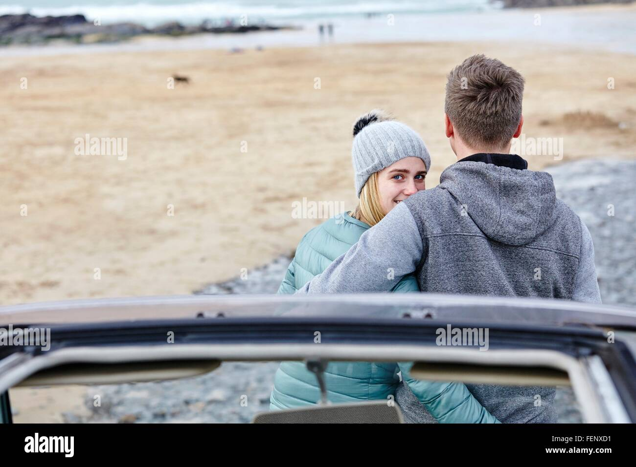 Young couple with arms around each other at beach, Constantine Bay, Cornwall, UK - Stock Image