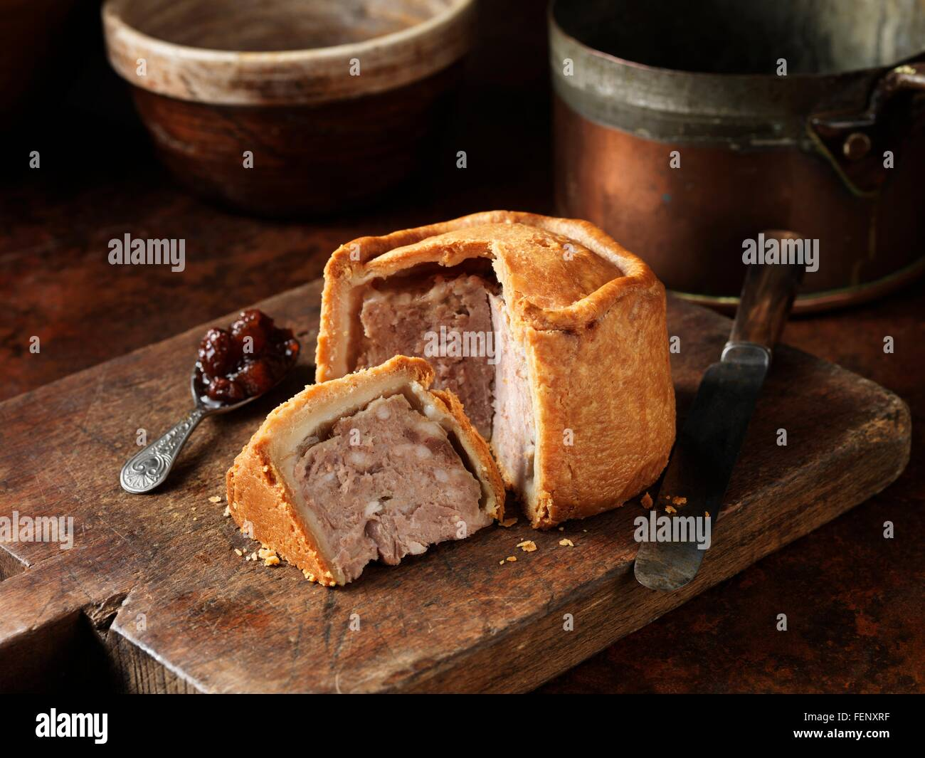 Sliced Melton Mowbray pork pie with spoonful of pickle on wooden cutting board - Stock Image