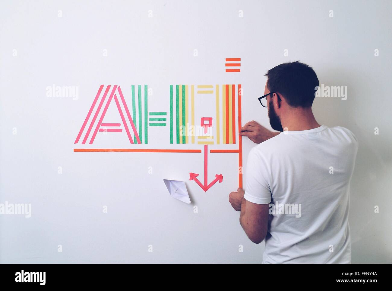 Rear View Of Man Creating Text From Multi Colored Papers On Wall At Home - Stock Image