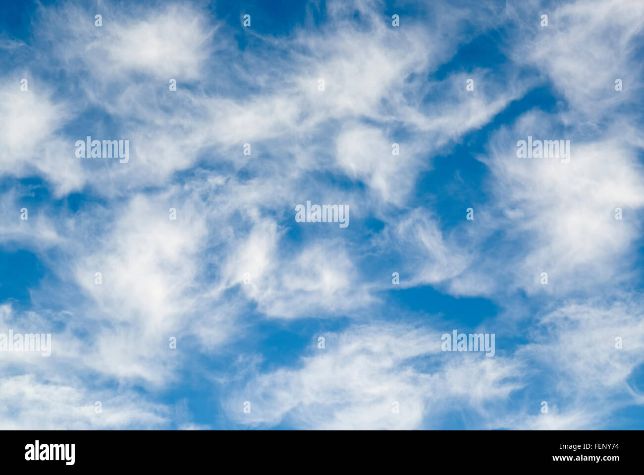 Cirrus cluds. White and wispy with mares Tales against clear blue sky - Stock Image