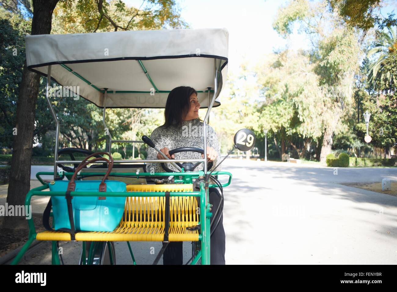 Mature woman sitting in golf buggy, looking away, Seville, Spain - Stock Image