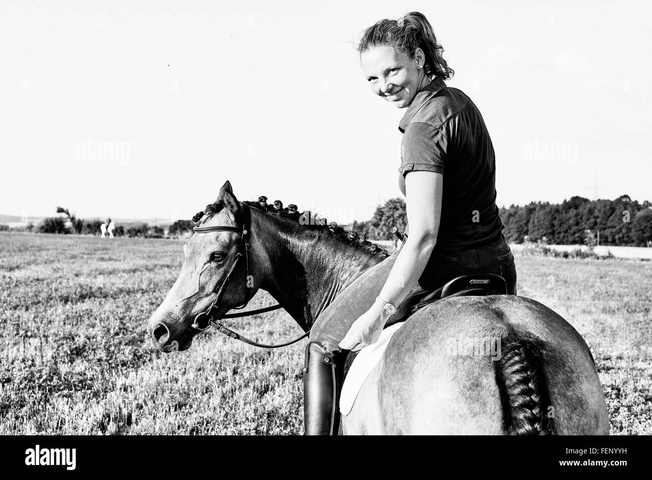 B&W portrait of woman riding horse in field and looking over her shoulder Stock Photo