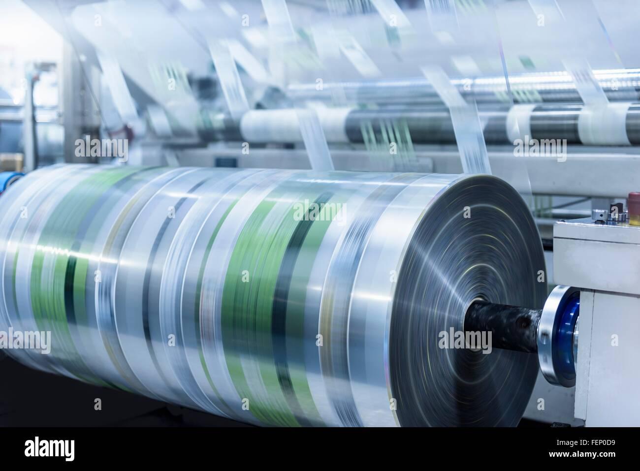Rolls of printed plastic film in food packaging printing factory - Stock Image