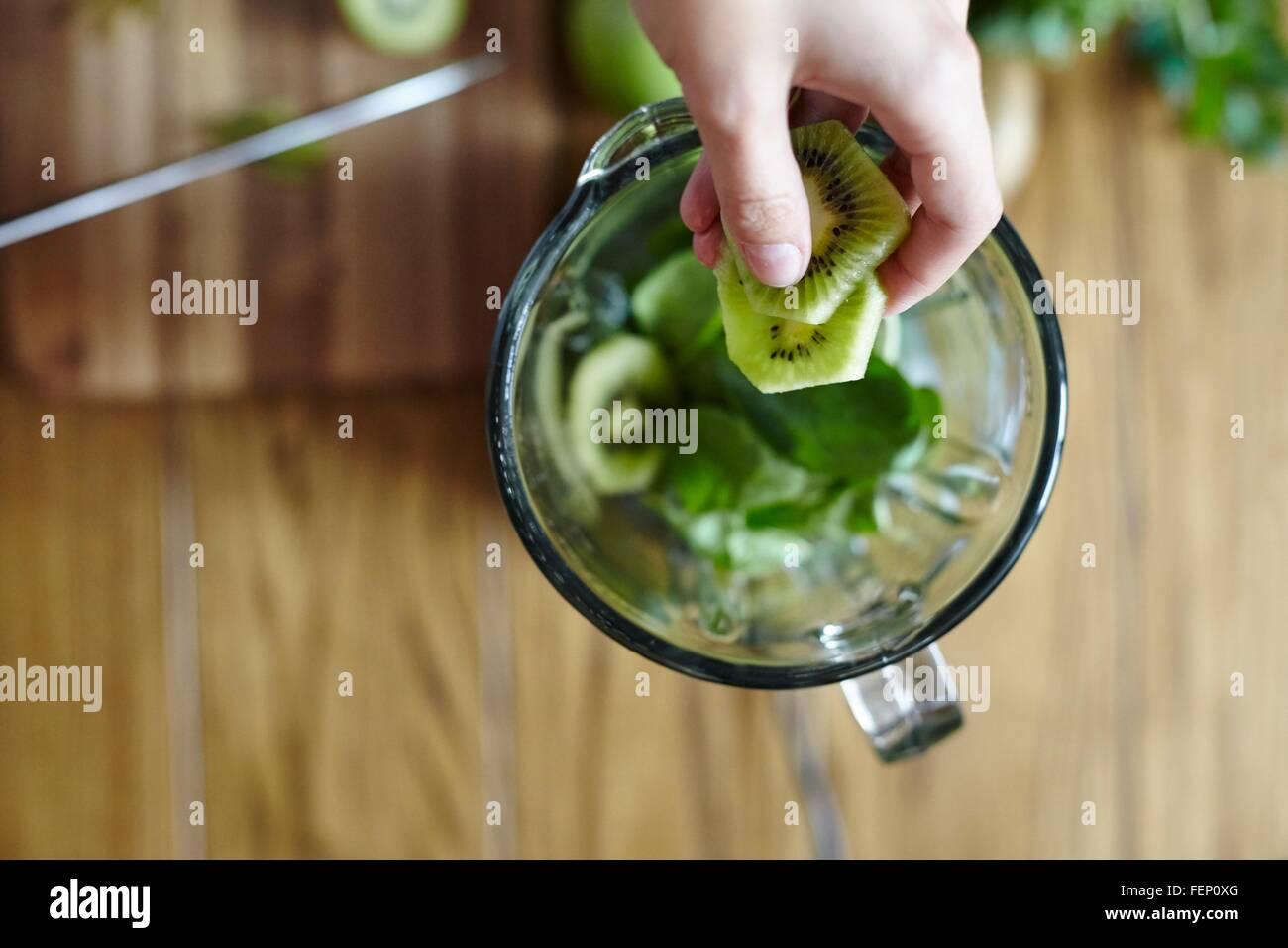 Woman holding sliced green kiwi over blender - Stock Image