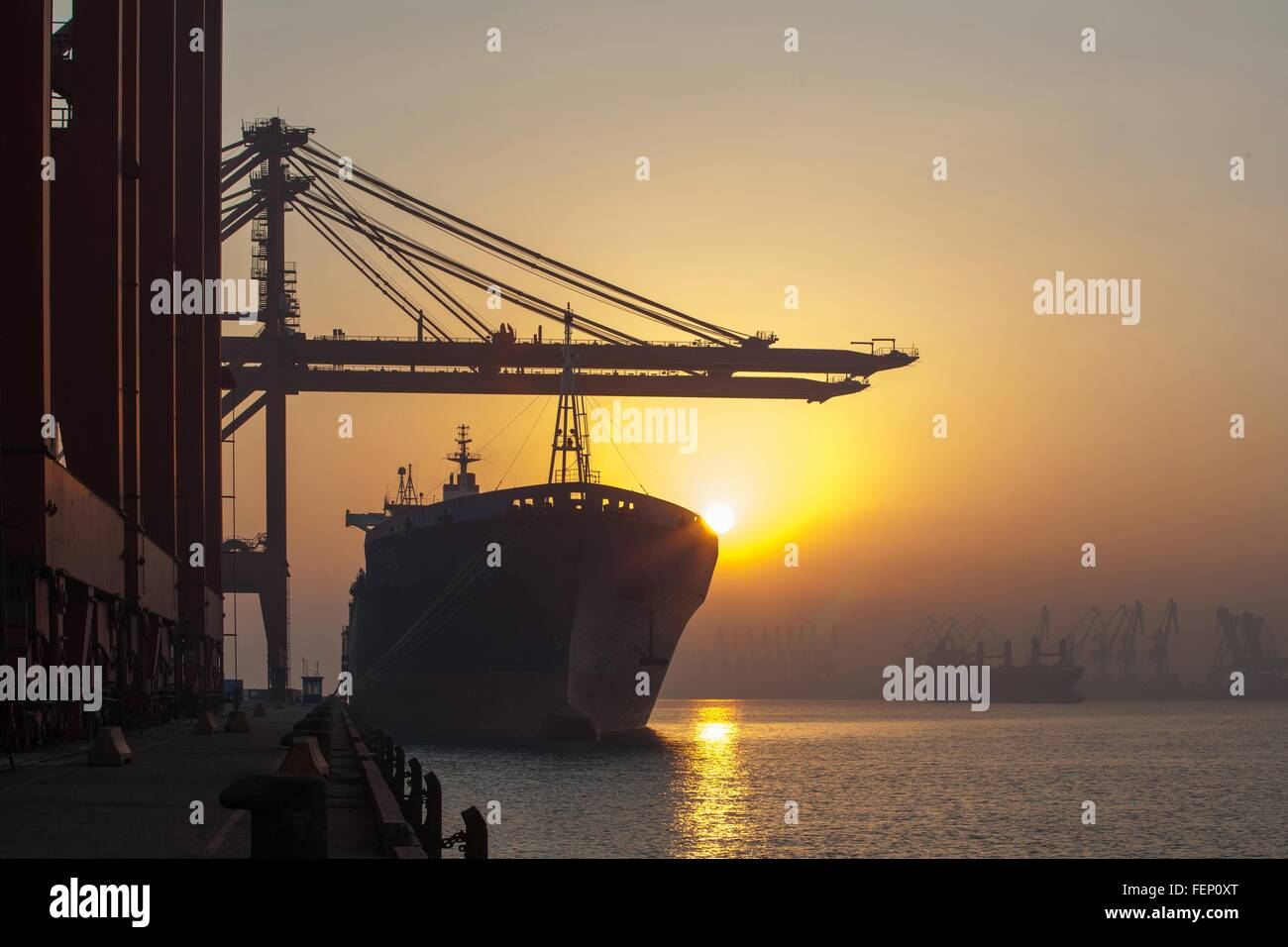 Container ship and cranes at port - Stock Image