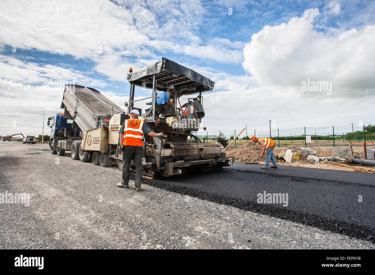 construction workers laying tar macadam asphalt - Stock Image