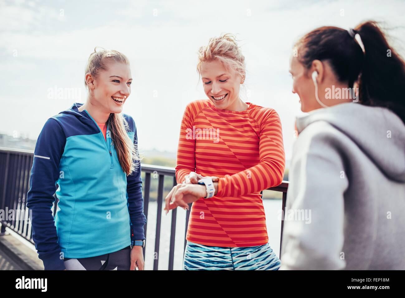 Three female runners coordinating time on city footbridge - Stock Image