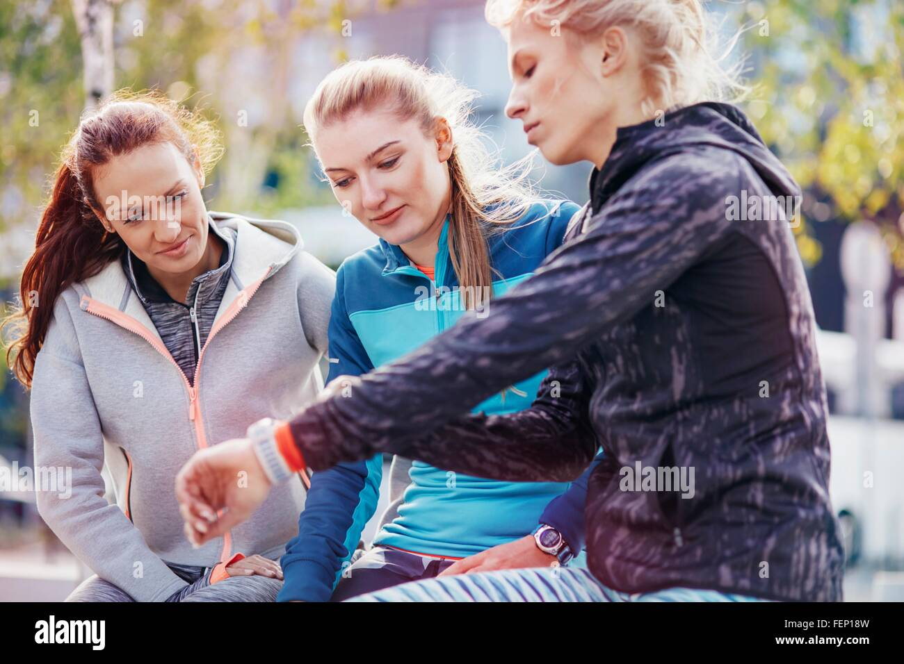 Three female runners coordinating times on smartwatch in city - Stock Image
