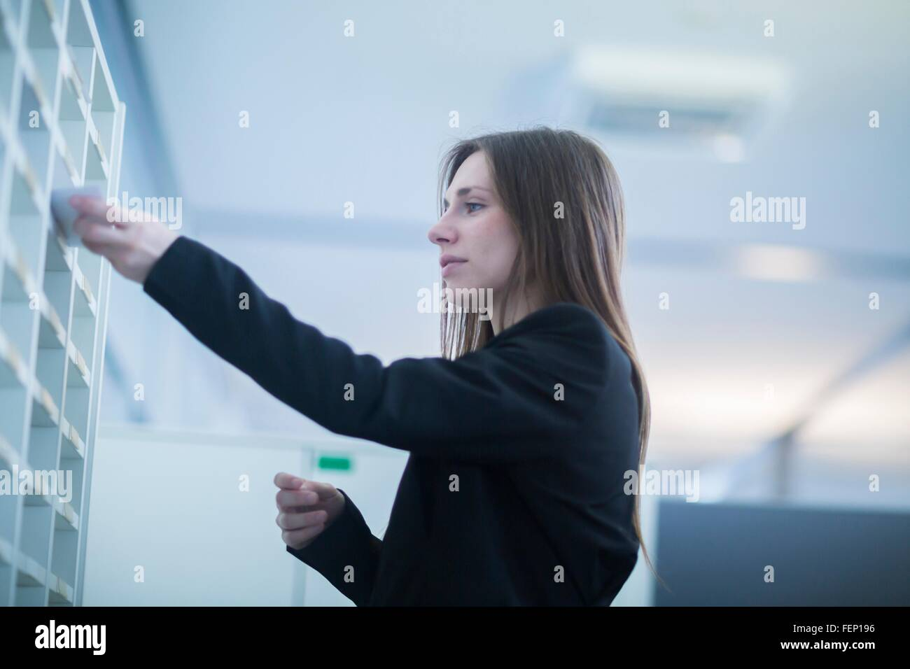 Low angle side view of young woman in office inserting paperwork into pigeon hole - Stock Image