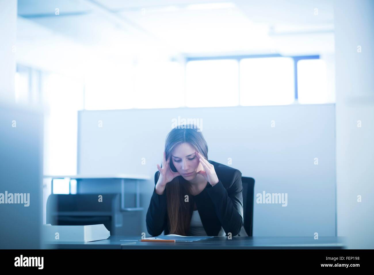 Young woman sitting at desk in office, head in hands looking down, stressed - Stock Image