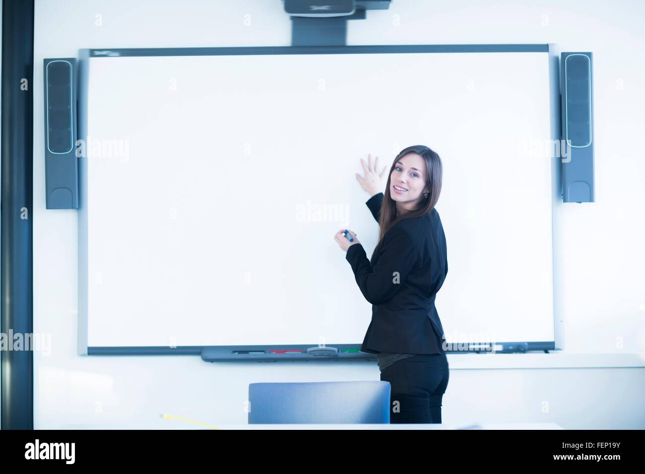 Young woman in office using whiteboard, looking over