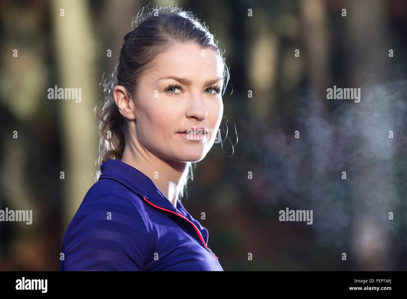 Portrait of young woman looking at camera, condensation from breath - Stock Image