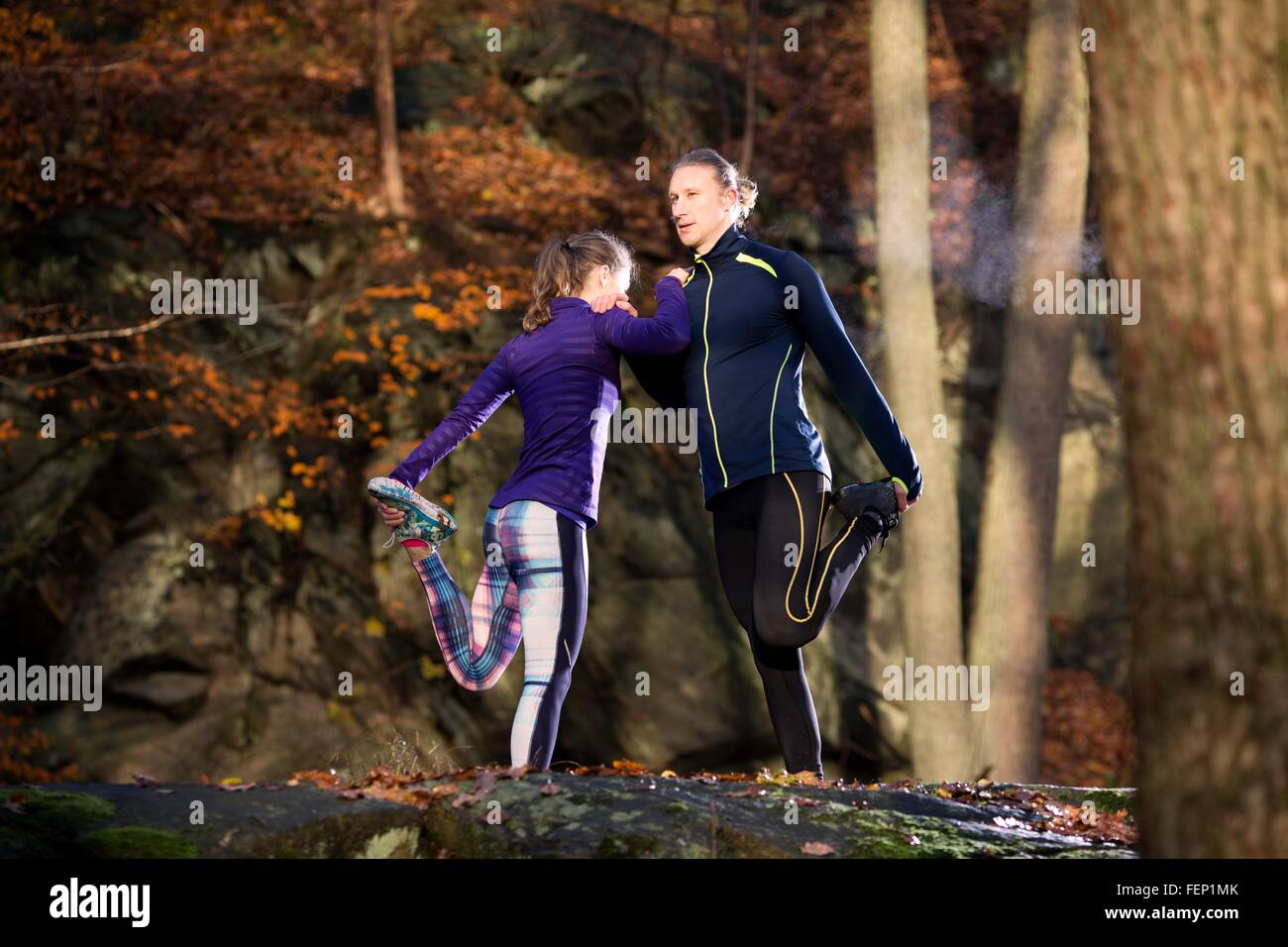 Couple in forest leaning against each other leg raised holding foot stretching - Stock Image