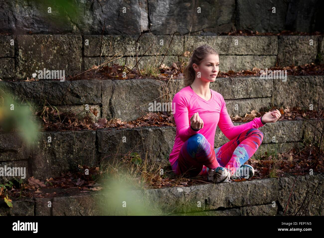 Young woman sitting cross legged on stone steps meditating looking away - Stock Image