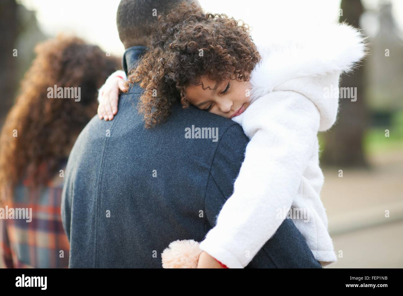 Rear view of father carrying sleeping daughter - Stock Image
