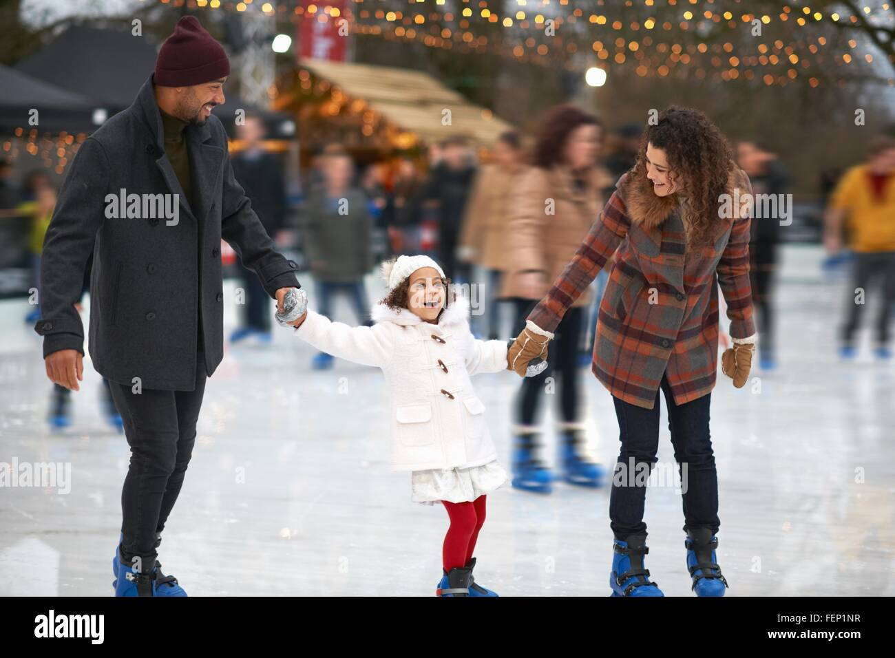 Girl holding parents hands ice skating, smiling - Stock Image