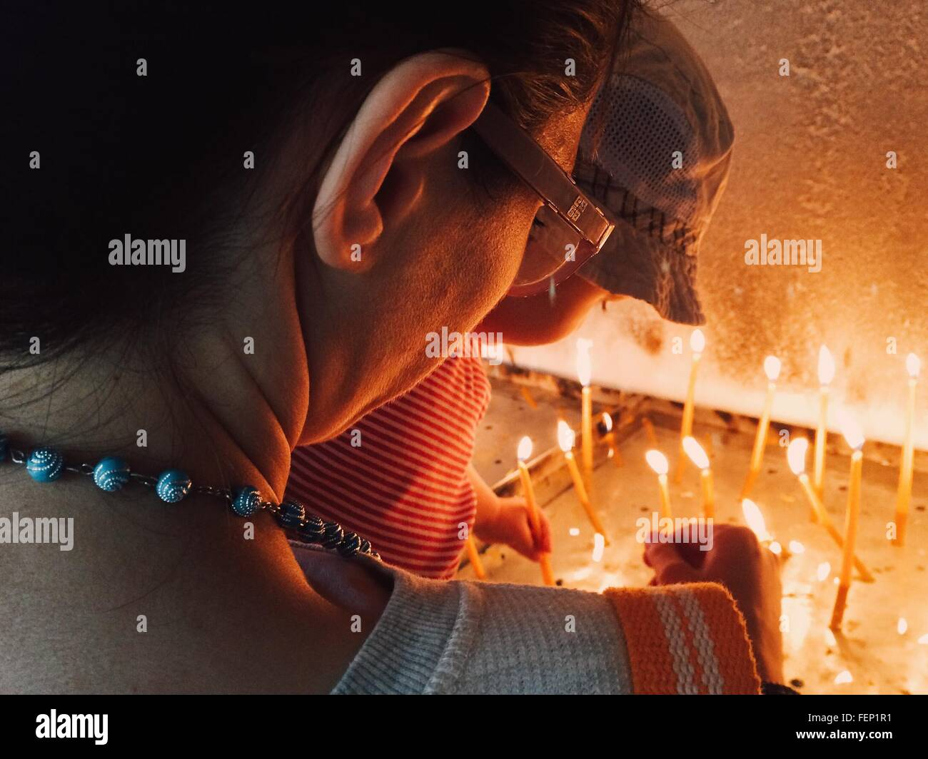 Rear View Of Mother With Child Lighting Candles In Church - Stock Image